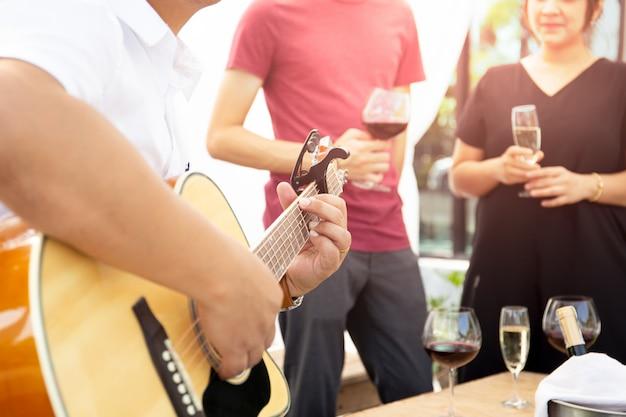 Gruppo di amici che hanno festa con vino rosso e suonare la chitarra all'aperto.