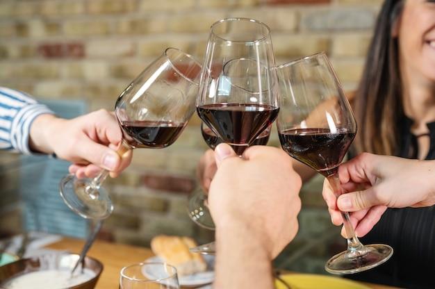 Gruppo di amici che tengono i bicchieri di vino, fare un brindisi.