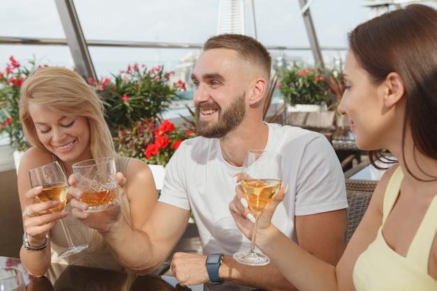Gruppo di amici che ridono, bevono vino insieme al bar sul tetto