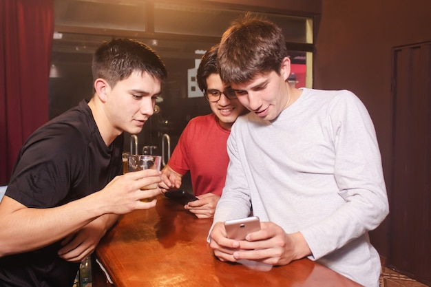 Un gruppo di amici che guardano il cellulare mentre bevono birra al bar.