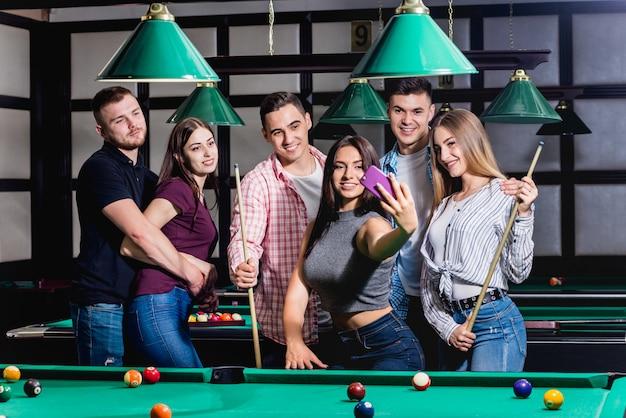 Un gruppo di amici fa un selfie al tavolo da biliardo. in posa con una stecca nelle loro mani.