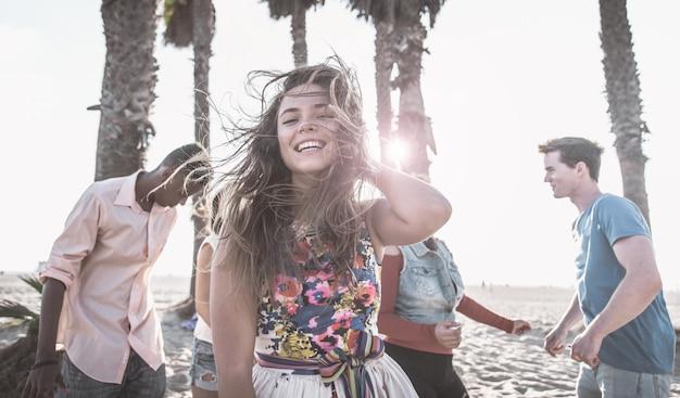 Gruppo di amici che fanno festa sulla spiaggia e ballano insieme