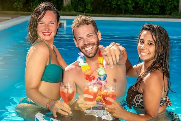 Gruppo di amici uomo e donna che fanno festa in piscina bevendo cocktail