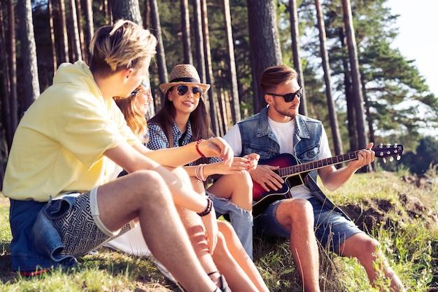 Gruppo di amici che fanno festa e ascoltano musica al tramonto.