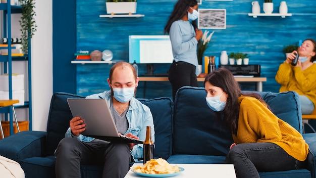 Gruppo di amici che pianificano un progetto utilizzando il laptop trascorrendo il fine settimana insieme in soggiorno indossando maschere protettive e rispettando il distanziamento sociale contro la diffusione del virus covid19 nella pandemia globale