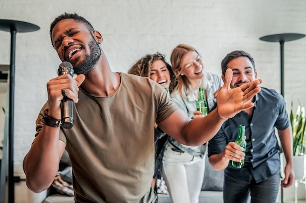 Gruppo di amici che giocano a karaoke a casa.