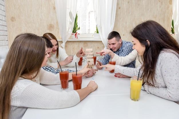 Gruppo di amici che giocano a torre nella caffetteria