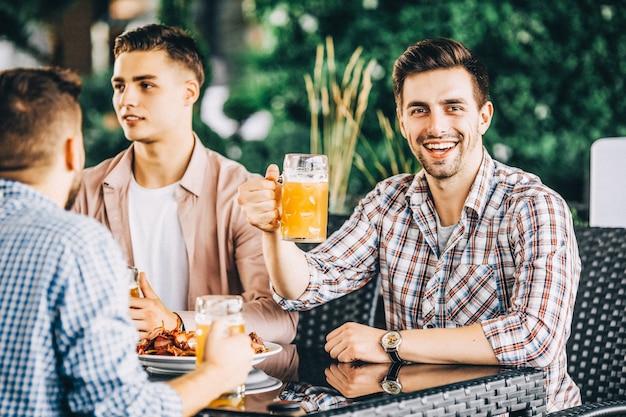 Gruppo di amici al pub, brindando e ridendo