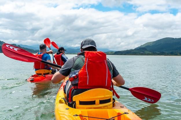 Un gruppo di amici in un percorso con il kayak in mare nel parco naturale di urdaibai, paesi baschi