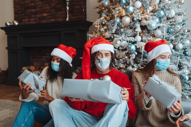 Gruppo di amici in cappelli della santa con doni nelle mani