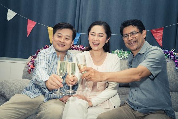 Raggruppi gli amici del partito felice della donna e dell'uomo senior con champagne a casa Foto Premium