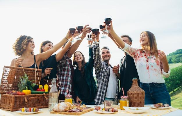 Gruppo di amici che passano il tempo a fare un picnic e un barbecue