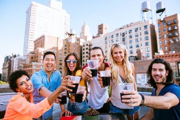 Gruppo di amici che passano insieme tempo su un tetto a new york city, concetto di stile di vita con persone felici
