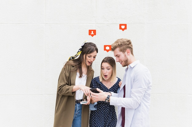Gruppo di amici in piedi vicino al muro di mandare un sms sul telefono cellulare