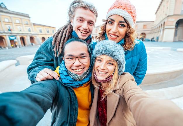 Gruppo di amici che prendono un selfie che indossa la maschera per il viso