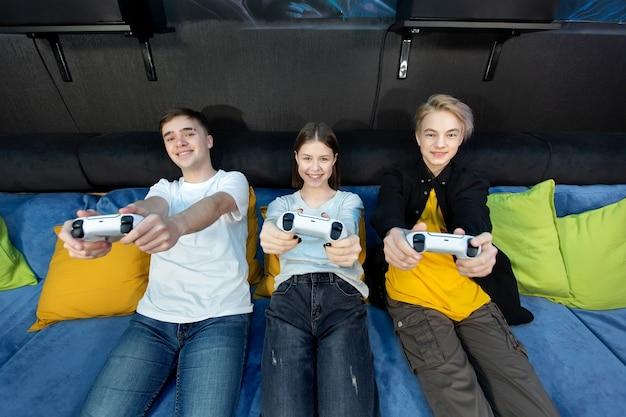 Gruppo di amici di adolescenti, ragazzi e ragazze che giocano ai videogiochi su una console in un club di gioco.