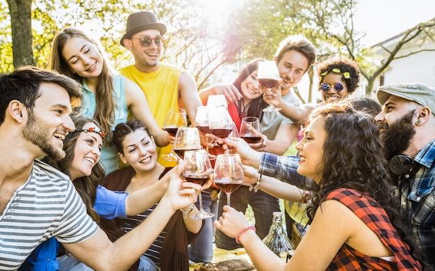 Gruppo di amici che tostano il vino rosso che si diverte a fare il tifo all'aperto al barbecue picnic - giovani che si godono l'estate insieme al pranzo in giardino - concetto di amicizia giovanile