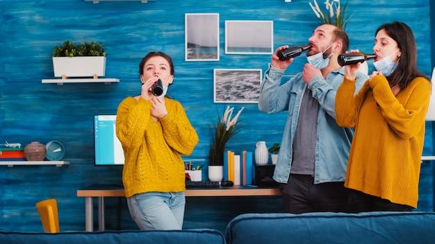 Gruppo di amici che brindano con bottiglie di birra indossando una maschera protettiva mantenendo le distanze sociali contro la diffusione del virus covid 19, godendosi il tempo in soggiorno