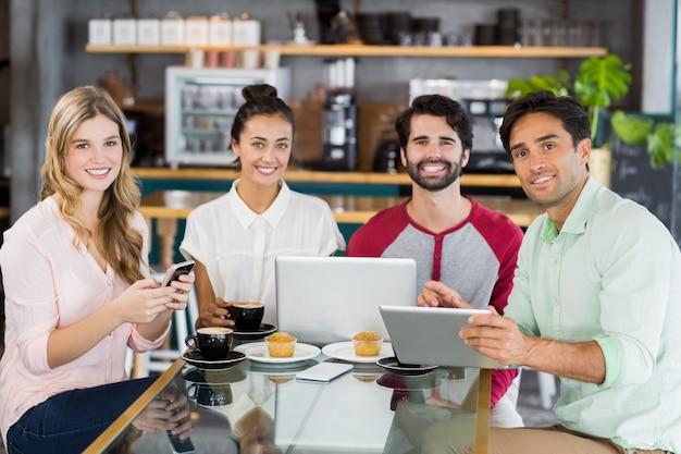 Gruppo di amici che utilizzano telefono cellulare, tablet digitale e laptop