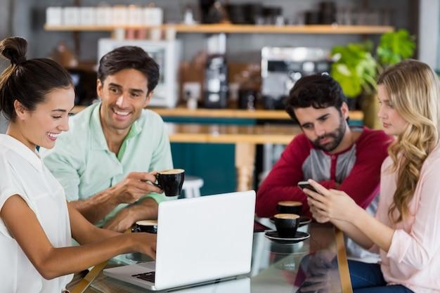 Gruppo di amici che utilizzano telefono cellulare e laptop