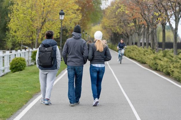Gruppo di amici che camminano nel parco di primavera