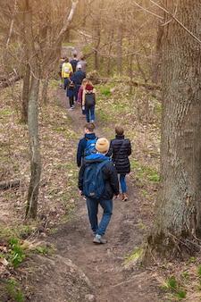 Gruppo di amici che camminano con gli zaini nella foresta di primavera dal retro