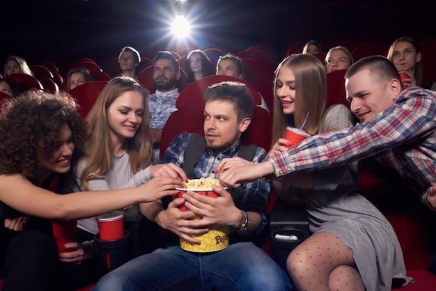 Gruppo di amici, guardare film e passare il tempo al cinema, tirando le mani a popcorn, avidità uomo arrabbiato guardando e abbracciando grande secchio. ragazza felice e ragazzi che vogliono mangiare popcorn gustoso al cinema.
