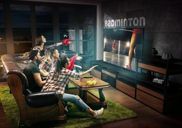 Gruppo di amici che guardano i giochi sportivi del campionato di partite di badminton in tv