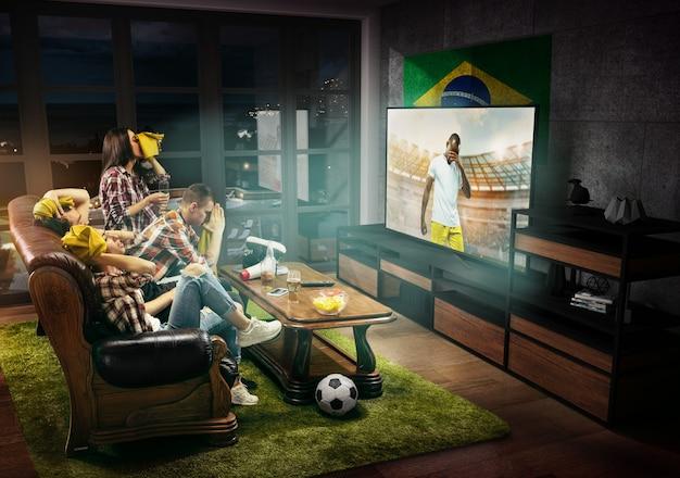 Gruppo di amici che guardano la tv, la partita di calcio, il campionato, i giochi sportivi. uomini e donne emotivi che tifano per la squadra di calcio preferita del brasile con bandiera. concetto di amicizia, competizione, emozioni.