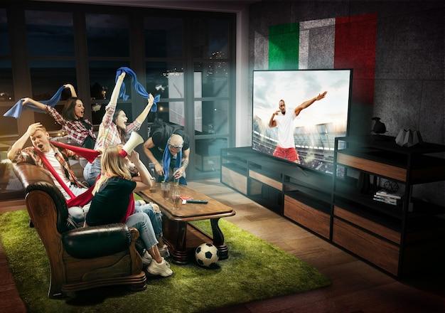 Gruppo di amici che guardano la tv, la partita, il campionato, i giochi sportivi. uomini e donne emotivi che tifano per la squadra di calcio preferita d'italia con la bandiera nazionale. concetto di amicizia, competizione, emozioni.