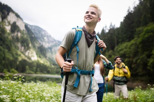 Gruppo di amici con zaini trekking insieme nella natura