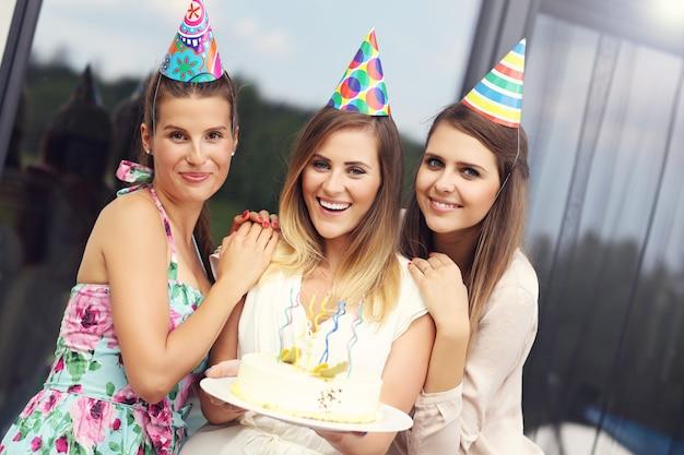 Gruppo di amici con torta che festeggia il compleanno