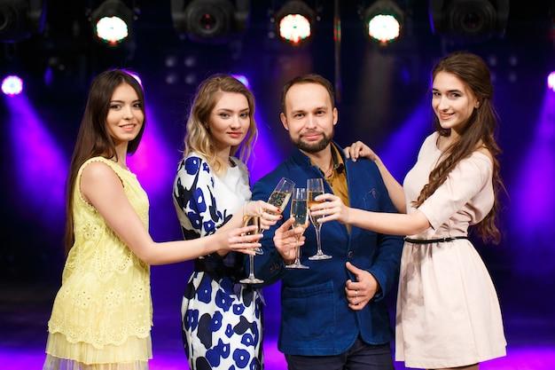 Gruppo di amici con bicchieri di champagne nel club
