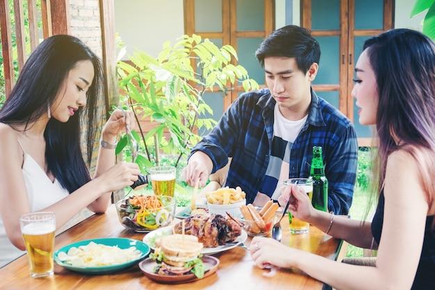 Gruppo di amici giovani asiatici partito e mangiare cibo