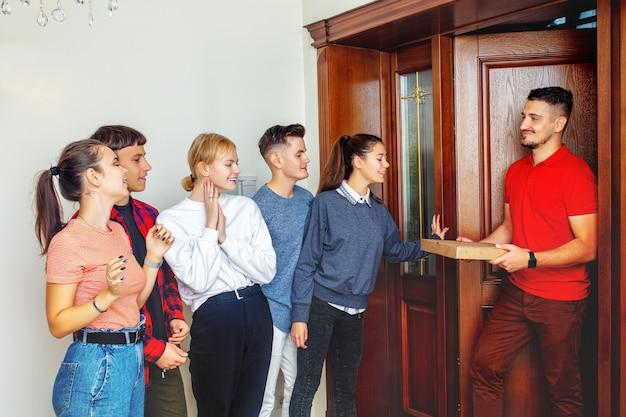Gruppo di amici giovani allegri felici incontrare un uomo di consegna pizza sorridente alla porta di casa