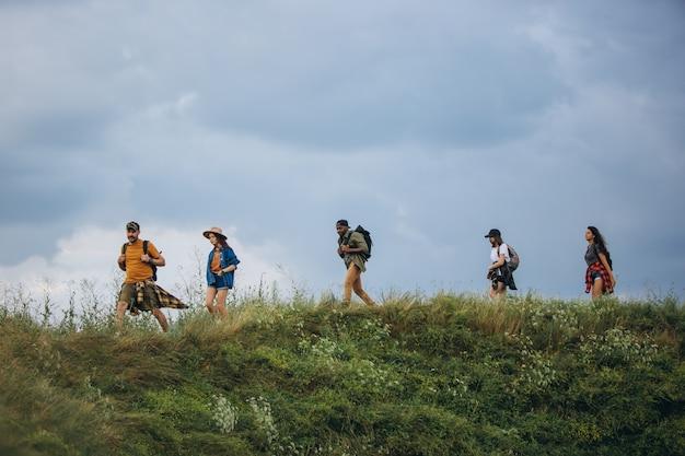 Gruppo di amici, giovani uomini e donne che camminano, passeggiano insieme durante un picnic nella foresta estiva