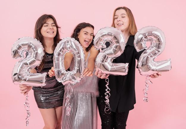 Un gruppo di amiche con palloncini d'argento a forma di numeri