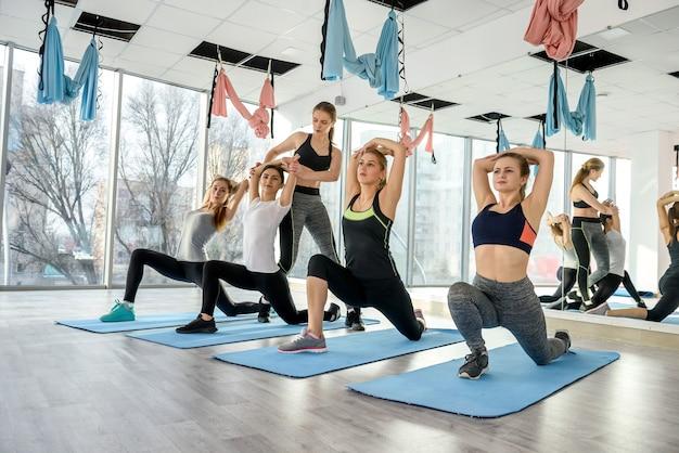 Il gruppo di ragazze è impegnato nel fitness sotto la supervisione dell'allenatore