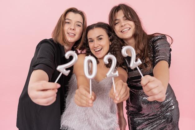 Un gruppo di ragazze tiene in mano le candele dei numeri su uno sfondo rosa