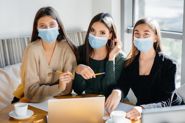 Un gruppo di ragazze in maschera si siede in un bar e lavora sui laptop. insegnare agli studenti.