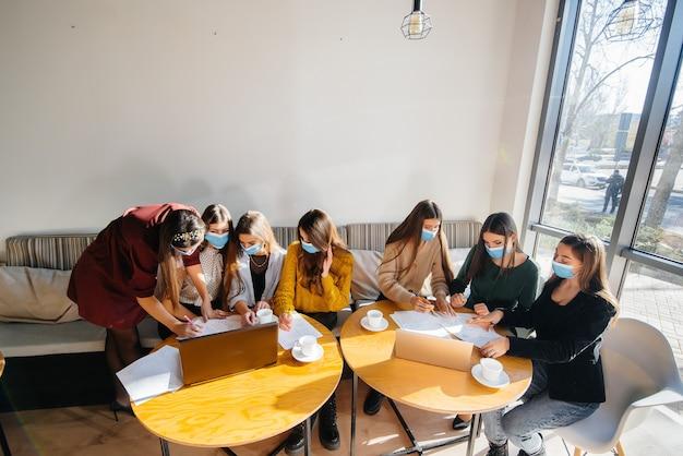 Un gruppo di ragazze in maschera si siede in un bar e lavora sui laptop