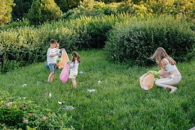 Un gruppo di ragazze con bambini al tramonto è impegnato nella raccolta dei rifiuti nel parco. cura dell'ambiente, riciclaggio.