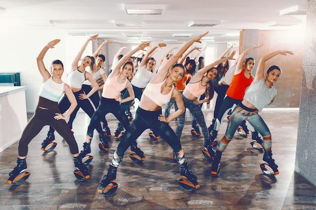 Gruppo di ragazze con abitudini sane che fanno esercizi in kangoo salta calzature. il tuo corpo può farlo, è la tua mente che devi convincere.