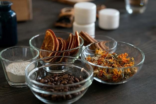 Gruppo di ciotole di vetro con chicchi di caffè, frutta secca e fiori e altri ingredienti per realizzare prodotti cosmetici naturali come il sapone