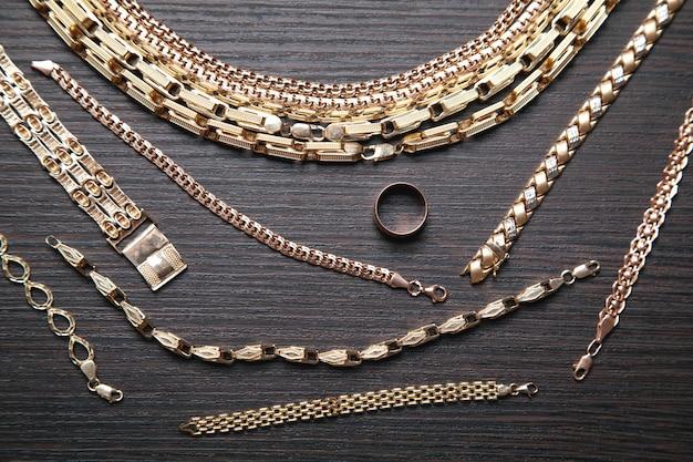 Gruppo di gioielli in oro su sfondo scuro.