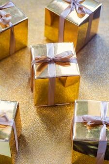 Gruppo di scatole regalo scintillanti d'oro, bella confezione oro sorpresa con fiocco su sfondo scintillante