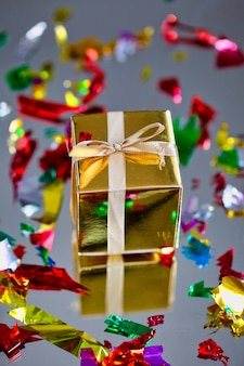 Gruppo di contenitori di regalo scintillanti dell'oro su fondo grigio con la riflessione e coriandoli