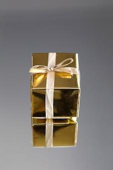 Gruppo di contenitori di regalo scintillanti dell'oro su fondo grigio con la riflessione