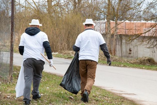Un gruppo di greenpeace raccoglie immondizia in un grande sacco della spazzatura mentre pulisce il territorio