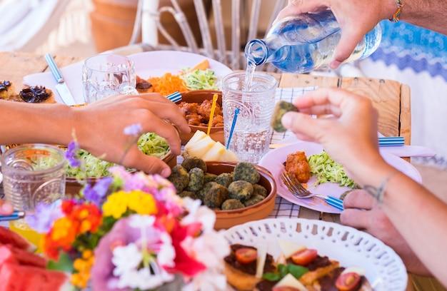 Gruppo di mani che condividono cibo e bevande popoli caucasici che si godono il brunch o il pasto insieme